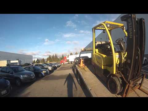 Moving Yellow Heavy Forklift on Flatbed Tow Truck