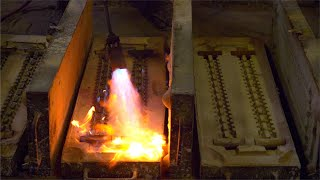 A worker is heating the molds for metal casting with a blowtorch