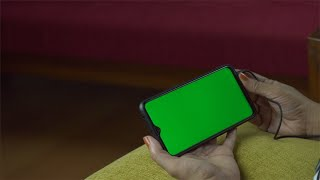 Woman hands browsing videos on the internet with her green screen smartphone