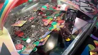 crazy gambling addict plays Wizard of Oz coin pusher game at nickel arcade