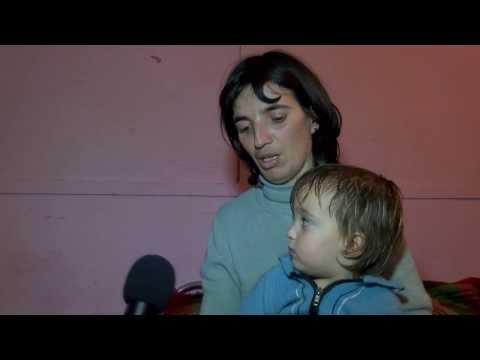 Социално слаба самотна майка върви пеш в преспите с малкото си дете.