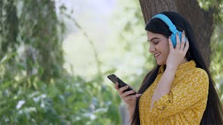 Young beautiful woman in headphones listening songs from her playlist - lifestyle concept