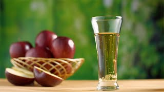 A glass of healthy apple juice with a basket of juicy apples in the background