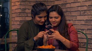 Two Indian teenagers smiling and posing while clicking selfies in a cafe/lounge