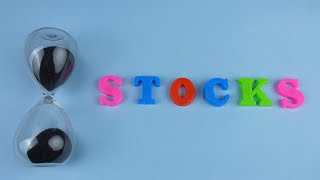 "Tilt shot of the word ""Stocks"" composed with colorful letters on a blue platform"