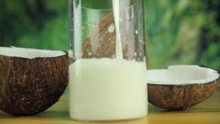 Closeup shot of pouring coconut milk in a transparent glass - vegan food concept