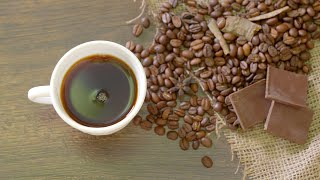 Cup of black coffee with coffee beans and chocolate on a wooden table