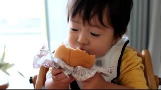 ハンバーガーを食べる赤ちゃんの笑顔が、とっても幸せそうでキュート!