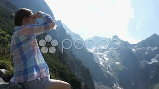 Woman at the mountain peak looking at beautiful view HD. Stock Footage