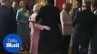 First Lady Michelle Obama touches the Queen during visit to Palace