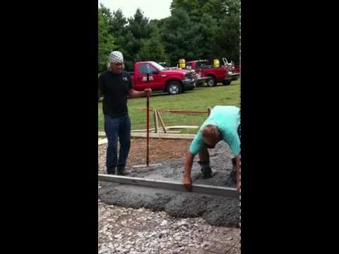 Papi pouring a concrete apron and sidewalk with Jim, Buddy and Miguel