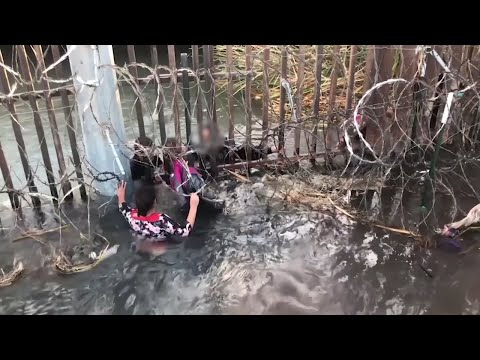 Dramatic Moment Migrants Cross Fence Along Canal At US-Mexico Border
