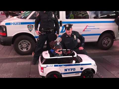 2 NYPD OFFICERS, INTERACTING WITH 2 CHILDREN DRESSED IN UNIFORM RIDING AROUND IN A TOY NYPD CAR.