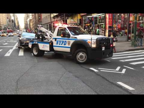 NYPD TOW TRUCK TOWING A CAR ON 8TH AVENUE IN THE MIDTOWN AREA OF MANHATTAN IN NEW YORK CITY.