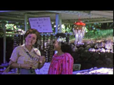 1964: Haole tourist woman Hawaiian Kukui Nut Lei from native merchant. KONA, HAWAII