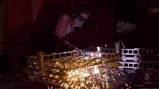 A worker welding two metal pieces in a factory
