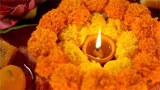 A lit up diya lamp during diwali puja celebration with flowers and sweets