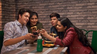 Young cheerful friends looking at the smartphone while having pizza in a cafe