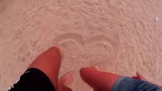 Рисуют сердце на песке ногами  Парень с девушкой нарисовали своими ногами сердце на морском песке