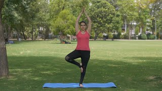 Young focused woman doing yoga asanas early morning in a park