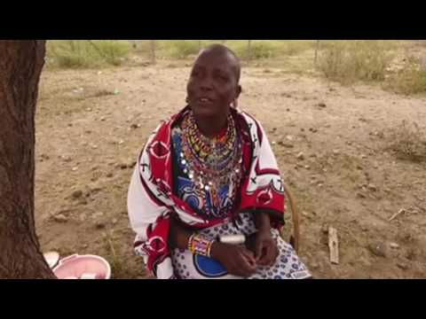 Maasai woman showing how to make a beaded necklace