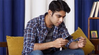 Young Indian man carefully making payment via his smartphone