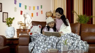 Loving parent reading a storybook to her little daughter during the winter season