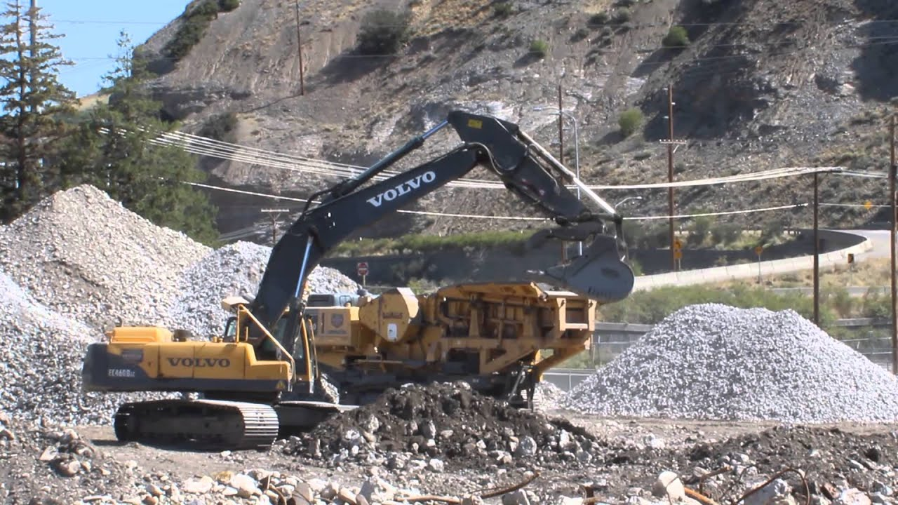 Volvo EC460 Excavator loading a rock crusher with medium size rocks while a Volvo EC360 crushes ...