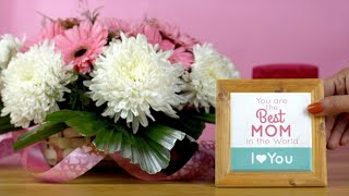 Closeup shot of a basket of pink and white flowers with a mother's day present