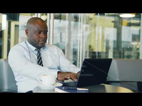 African American businessman thinking, printing and working on his laptop in glassy cafe during