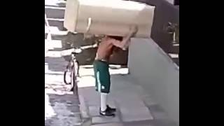 Guy rides off with refrigerator on his back.