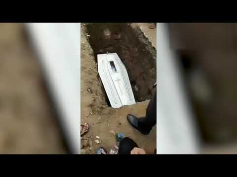 Corpse Waves To Mourners Through Coffins Glass Panel