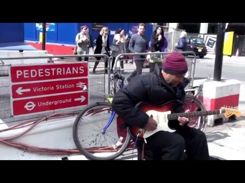 Street musician plays a cheerful melody on guitar at Victoria station - London