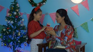 Cute little kid gifting her beautiful mother a special Christmas present on Christmas in India