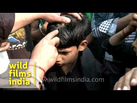 Young Shiite Muslim boy cries as an elder makes a cut on his forehead during Muharram