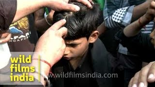 Young Shiite Muslim cries as an elder makes a cut on his forehead during Muharram