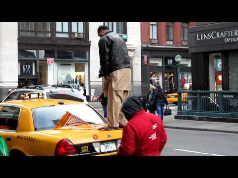 Cab Driver worships on trunk of his cab on Broadway NYC