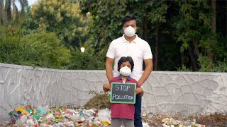 "Tilt shot of young father and son of India standing with a ""Stop Pollution"" signboard"