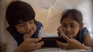 Indian siblings using tablet pc under the blanket at night - Technology invasion