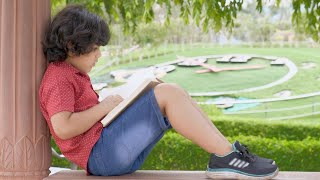 Young sincere schoolboy reading his storybook while sitting in a park - childhood education