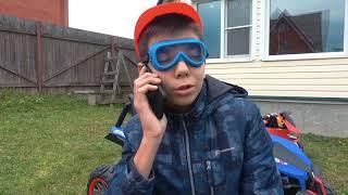 Малыш играет с игрушечной полицейской машиной и притворяется что поставил гигантское колесо