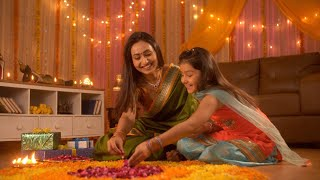 Diwali festival decoration - Happy mother and daughter decorating rangoli with rose petals