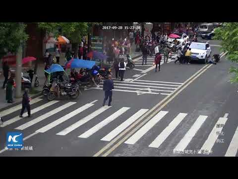 Passers-by lift car to save boy trapped under the vehicle, in Hunan, China