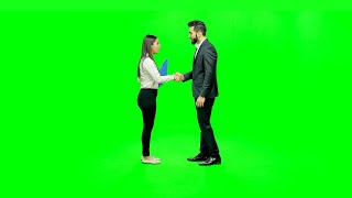 Young boy and girl dressed professionally crossing each other and handing over a file against the green screen