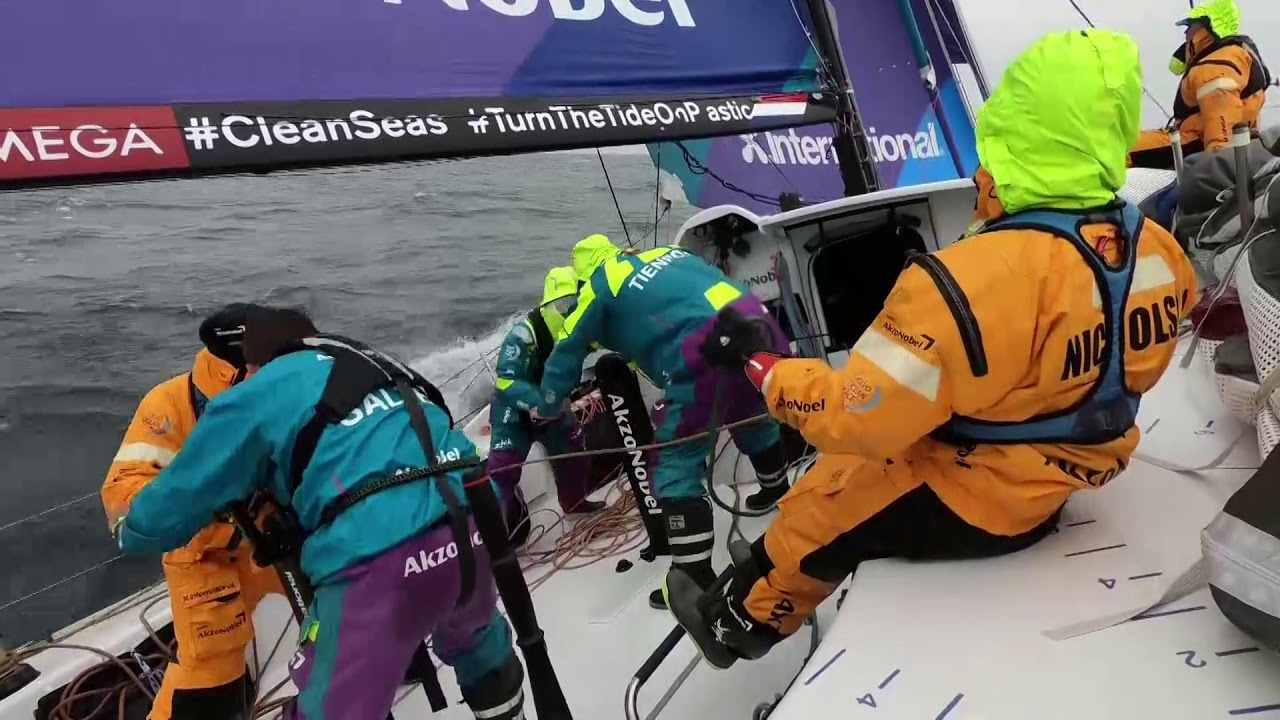 "Drone shot of AkzoNobel triple-heading with the J0. Jules through the hatch: Think Turn the Tide might have gone to the J1. Shot of chart screen. Jules and Nicho talk about wind, sail selection. ""Just starting to build a bit now, into J1 country."" Martine looks through binoculars. Crew discusses other boats and their sail selection: Vestas, Dongfeng. Sail change. Nicho: Just changed from the J0 to the J1. Not an easy change, becaue the bowman has to hank on the new sail forward; he usually complains about that a bit. Don't know why. Goes on to talk about competion. ""Slightly smaller sail, go a bit higher. Slightly smaller sail, but it gets us where we need to be. Next question is, if it's too windy for this sail when we get to the corner, we'll have to do another heinous sail change, and he'll probably change again. [He asks Luke on the helm if he thinks the bowman will complain; Luke agrees.] Nicho: That's why once in a blue moon you go up there with him so then he can't complain... Won't be doing that again. Slomo pole cam footage from outboard of Nicho on the bow with someone (presumably Brad) hooking up and hoisting the J1."