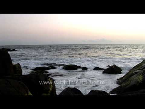 Waves crashing against rocks on a beach, Kerala