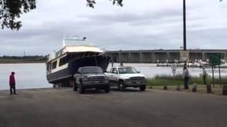 Two Dodge trucks pulling 60,000 lbs up a boat ramp