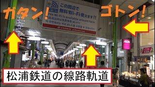 ちょうど松浦鉄道が商店街の建物をダイナミックに貫く線路軌道を通過したので走行音が鳴り響く佐世保の三ヶ町商店街の風景