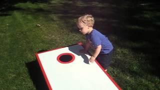 Toddler playing cornhole