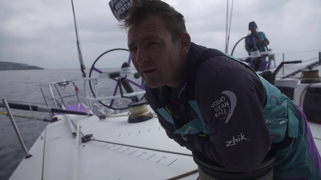 Drone shot alongside as AkzoNobel sails in 15 knots of wind. Looks like they have a J0 and J3 up; MH0 and J2 (maybe?) are up but furled. Maybe shifting gears in expectation of falling wind? Brad goes out to the MH0 clew to take the lazy sheet off. Nicho talks about them expecting lighter winds as they approach the Irish coast. Beautiful drone shot with grassy hillside in the foreground and AkzoNobel and two other competitors (TTToP and Vestas, I think, from the tracker) behind them approaching the coast. Jules talks strategy in the cockpit. Jules: It's pretty rugged, and the water's pretty fresh and clean, and there's lots of granite that's been weathered by lots of storms, so there's lots of caves and arches. Drone shot flying through a sea cave (!) with AkzoNobel visible beyond. Then another shot of a small opening in the rock with a red-sailed boat (MAPFRE?) beyond. Jules: Pretty green because it rains a lot. And there's lots of good pubs. That's why I like it. He talks about the fleet, and compression; first 6 boats all within 3-5 miles of each other. Emily: Quite cool to see the geography of Ireland. Usually the wather's bad so you don't see it that much. Justin on the bow with Fastnet rock behind him. Drone shot with ridge and AkzoNobel beyone. Nicho: third or fourth at the moment; same as we are overall. Way forward for us to score as high up as possible, but certainly conditions ahead could have boats doing damage. We need a little of that to help us get on the podium overall. Just keep pushing the boat and sailing as quick as we can.